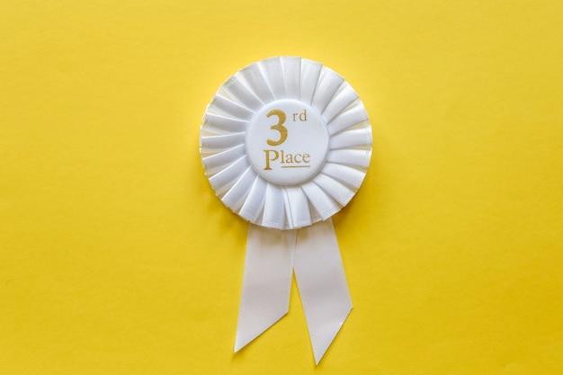 Roseta de fita branca de 3º lugar em amarelo
