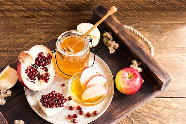 Rosh hashaná, conceito de feriado de ano novo judaico com símbolos tradicionais, maçãs, mel, romã em uma mesa de madeira.