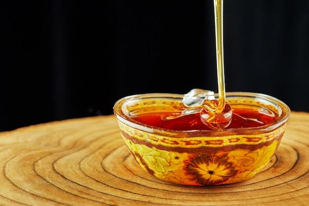 Rosh hashaná - conceito de feriado de ano novo judaico. um fluxo de mel flui para uma tigela em um suporte de madeira.