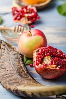 Rosh hashaná (hashana) - conceito de feriado de ano novo judaico. símbolos: pote de mel e maçãs frescas com romã e shofar - chifre sobre um fundo azul. copie o espaço para texto. vista de cima