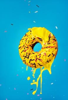 Rosquinha amarela sobre um fundo azul