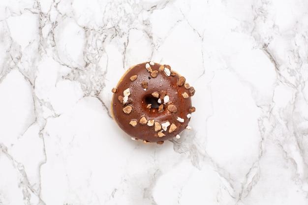 Rosquinha de chocolate doce na superfície de mármore isolada plana leigos, minimalismo, comida