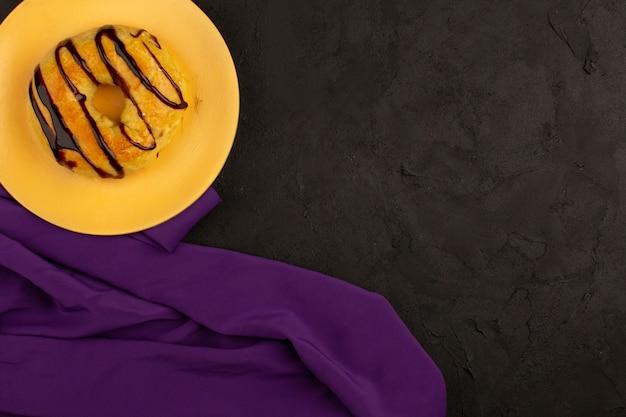 Rosquinha de vista superior dentro da placa laranja na mesa escura