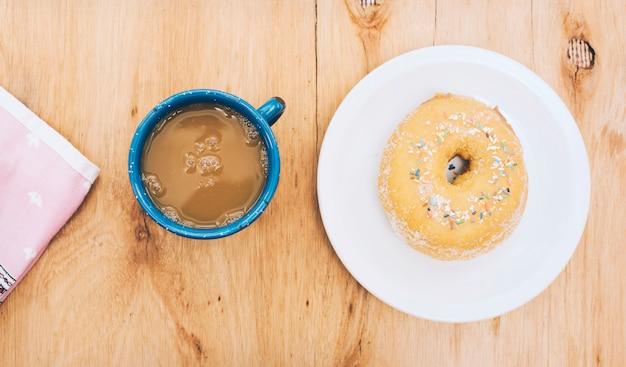 Rosquinha deliciosa no prato; xícara de café e guardanapo no pano de fundo texturizado de madeira