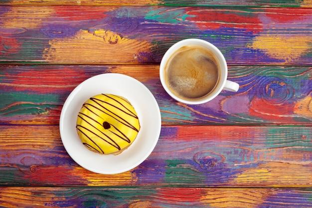 Rosquinha fresca com café na superfície de madeira, vista superior