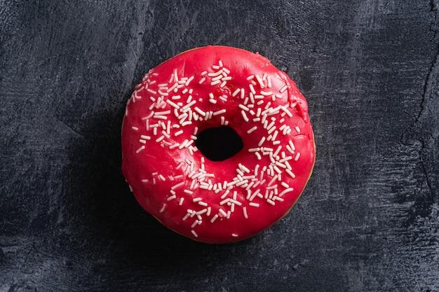 Rosquinha rosa com granulado, comida de sobremesa doce envidraçada no escuro