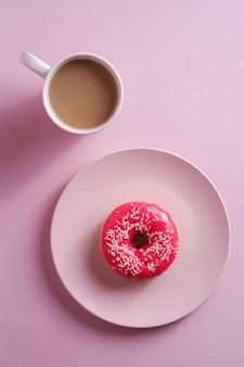 Rosquinha rosa com granulado no prato perto de xícara de café, comida de sobremesa doce vitrificada