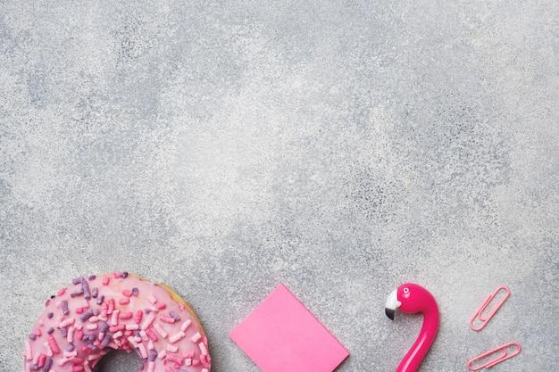 Rosquinha rosa e caneta flamingo. fundo com copyspace