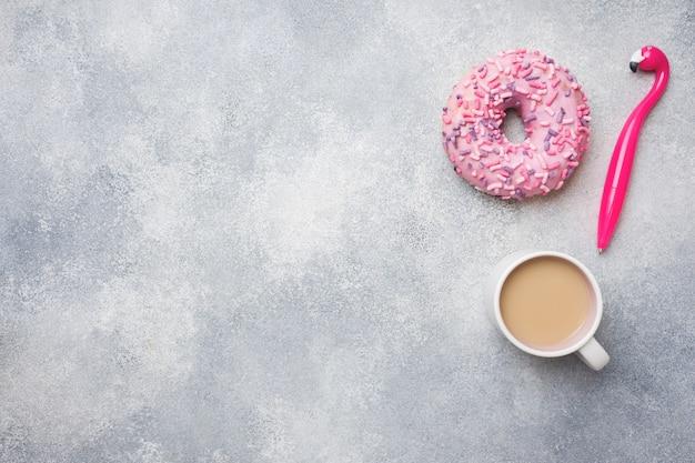 Rosquinha rosa e xícara de café flamingo caneta. vista superior plana leigos. fundo com copyspace