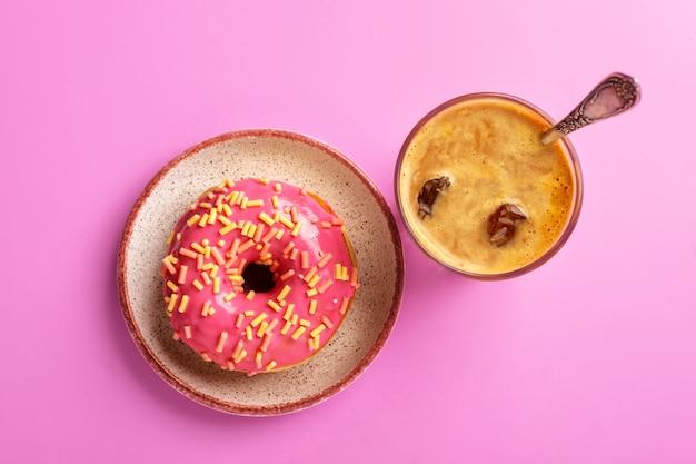 Rosquinha rosa em um prato e café gelado, vista superior, em um rosa.
