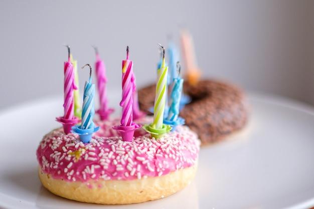 Rosquinhas coloridas com cobertura rosa e chocolate com velas para festa de aniversário