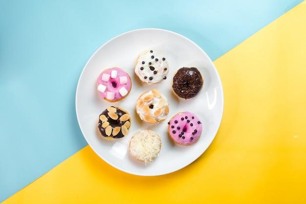 Rosquinhas coloridas, servidas em um prato branco sobre um fundo criativo