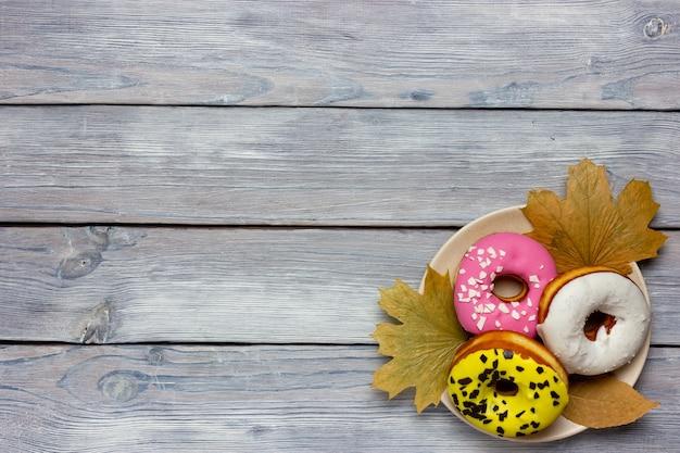 Rosquinhas coloridas sobre uma folha de bordo amarela de outono em uma vista de mesa de madeira