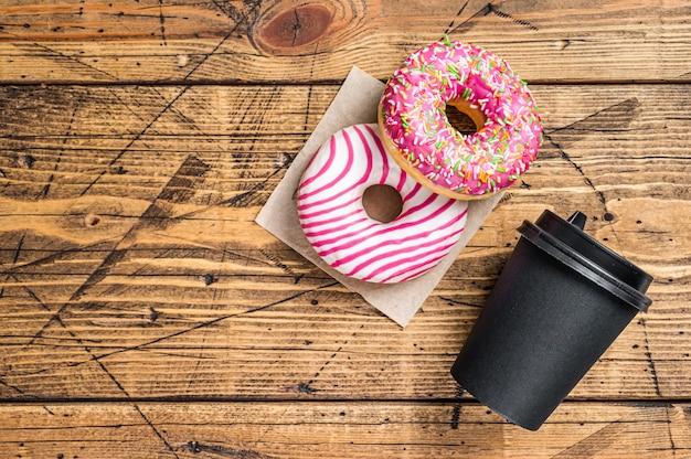 Rosquinhas com cobertura rosa na mesa da cozinha com café. fundo de madeira. vista do topo. copie o espaço.