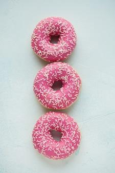 Rosquinhas cor de rosa em açúcar de confeiteiro.