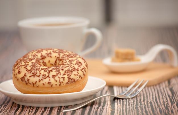 Rosquinhas de sobremesa e xícara de café quente na mesa de madeira