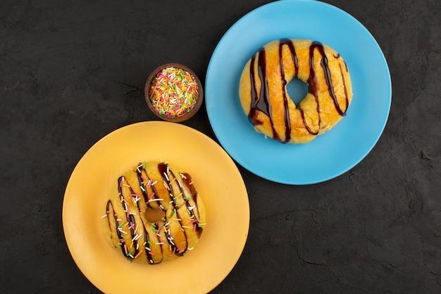 Rosquinhas de vista superior chocolate dentro de placas coloridas no chão escuro