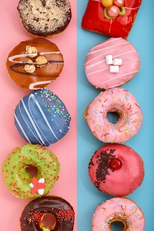 Rosquinhas doces sobre um fundo azul e rosa. rosquinhas sortidas, borda cor de fundo azul e rosa.