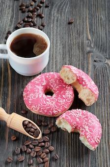 Rosquinhas frescas rosa com granulado e uma xícara de café na velha mesa de madeira