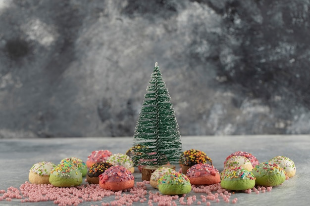 Rosquinhas pequenas doces coloridas com granulado e uma xícara de chá.