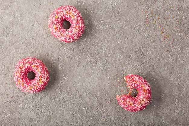 Rosquinhas rosa em concreto cinza