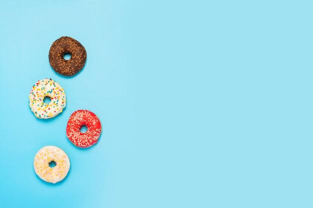 Rosquinhas saborosas de diferentes tipos em uma superfície azul. conceito de doces, padaria, bolos. . vista plana, vista superior