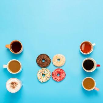 Rosquinhas saborosas e copos com bebidas quentes, café, cappuccino, chá sobre uma superfície azul. conceito de doces, padaria, bolos, café, reunião, amigos, equipe amigável. quadrado. vista plana, vista superior