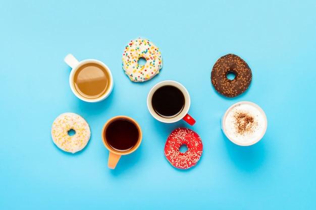 Rosquinhas saborosas e copos com bebidas quentes sobre uma superfície azul. conceito de doces, padaria, bolos, café, amigos, equipe amigável. vista plana, vista superior