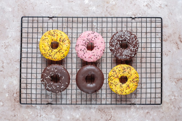 Rosquinhas variadas com cobertura de chocolate, glacê rosa e granulado.