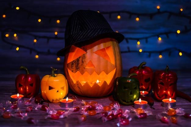 Rosto assustador de jack-o-lantern, pimentas com faces curvas e assustadoras, velas, chamas, doces, luzes, luz vermelha mística