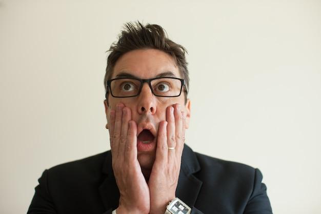 Rosto aterrorizado de homem de negócios em óculos