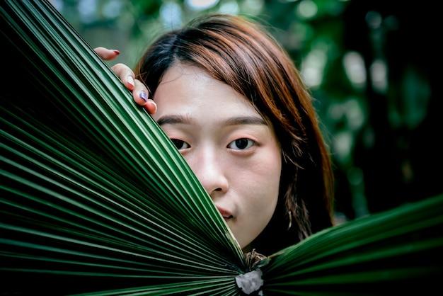 Rosto atraente de mulher asiática se escondendo atrás de folhas verdes de palmeira