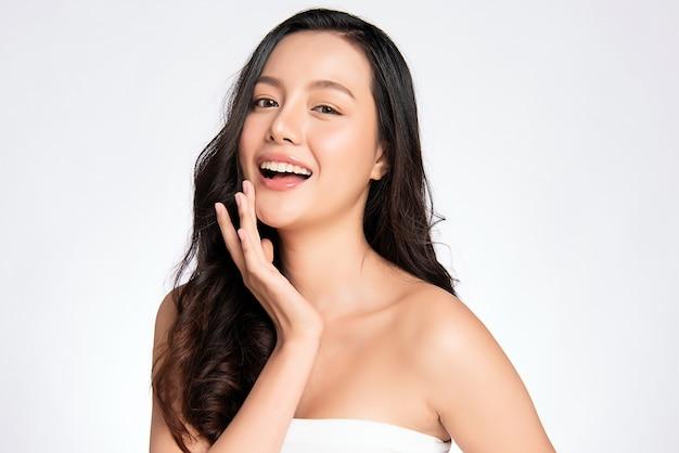 Rosto bonito. mulher asiática sorridente tocando retrato de pele saudável. modelo linda garota feliz com pele facial hidratada brilhante e maquiagem natural,