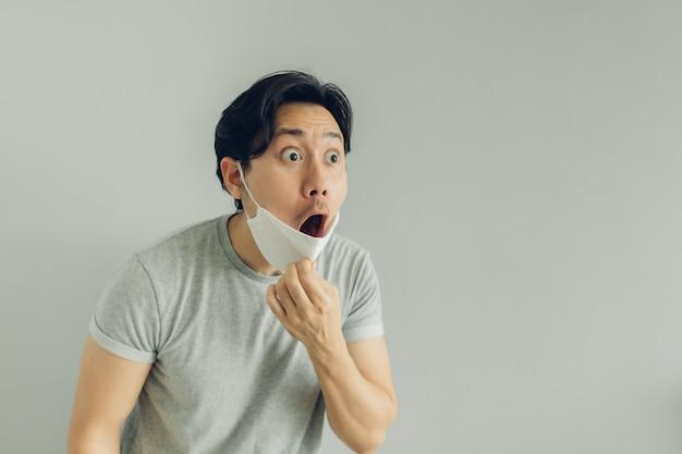 Rosto chocado e surpreso de homem vestindo máscara higiênica branca em camiseta cinza.