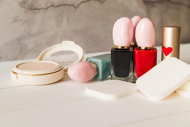 Rosto cosmético compacto em pó com esponjas; garrafa de esmalte e batom na mesa