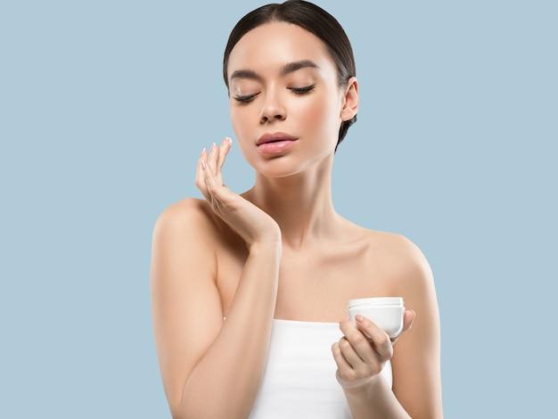 Rosto creme mulher cosmética pele saudável cuidados beleza retrato isolado no branco cor de fundo azul