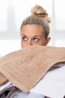 Rosto curioso de mulher espreitando sobre pilha de roupas