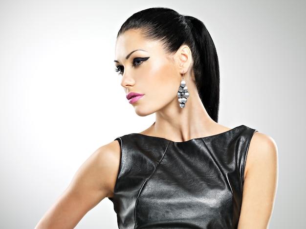 Rosto da bela mulher sexy com maquiagem de moda glamour dos olhos e penteado de brilho. retrato da menina adulta caucasiana em estúdio