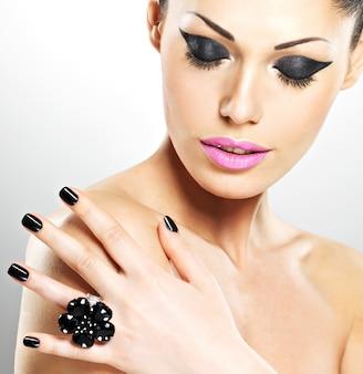 Rosto da bela mulher sexy com unhas pretas e lábios cor de rosa. garota sexy com maquiagem fashion