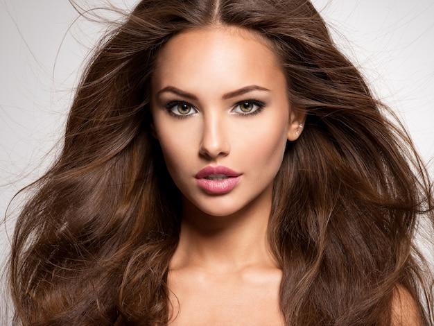 Rosto da mulher bonita com longos cabelos castanhos posando no estúdio