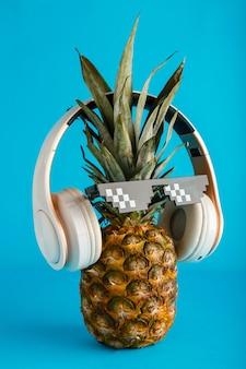 Rosto de abacaxi feliz ouvindo música criativa rosto de abacaxi engraçado usando óculos escuros headphon