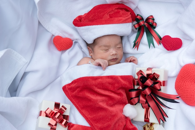 Rosto de bebê recém-nascido dormindo no chapéu de natal com caixa de presente do papai noel