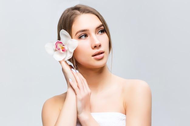 Rosto de beleza da jovem mulher bonita com flor. garota em cinza. cosmetologista.