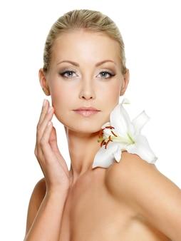 Rosto de beleza da jovem mulher bonita com flor. pele comovente feminina. garota no espaço em branco