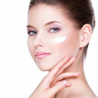 Rosto de beleza de jovem com creme cosmético em uma bochecha. conceito de cuidados com a pele. retrato do close up isolado no branco.