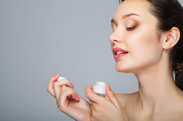 Rosto de beleza de mulher com creme cosmético no rosto