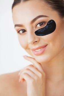 Rosto de beleza de mulher com máscara sob os olhos. mulher bonita com maquiagem natural e manchas de colágeno preto na pele facial fresca