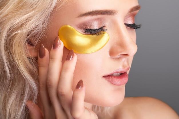 Rosto de beleza de mulher com máscara sob os olhos.