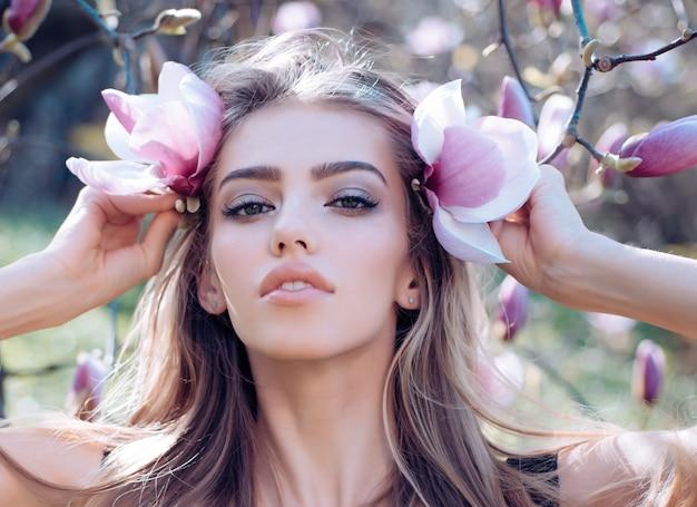 Rosto de beleza de mulher de primavera em flor de magnólia. maquiagem natural de mulher sensual. garota sexy.