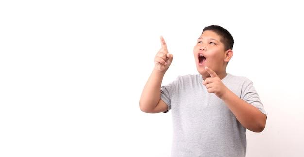 Rosto de choque e surpresa do menino apontando o dedo no fundo branco.